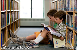 Young boys reading books in the library